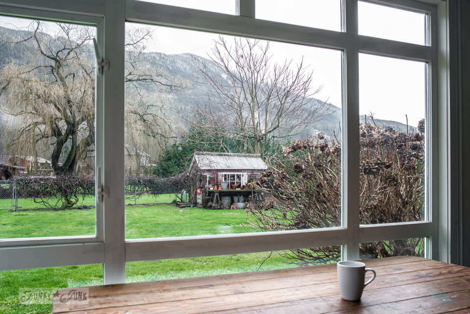 Picture window facing a mountain backyard view with a rustic shed in winter