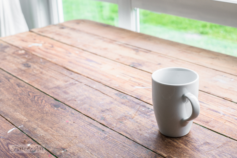 White mug on a reclaimed wood topped farm table