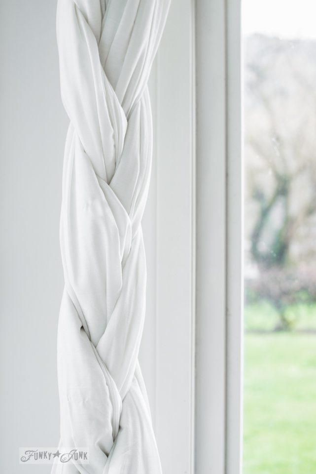 Braided white sheet curtains as tie backs hung from a pipe curtain rod in a photo studio