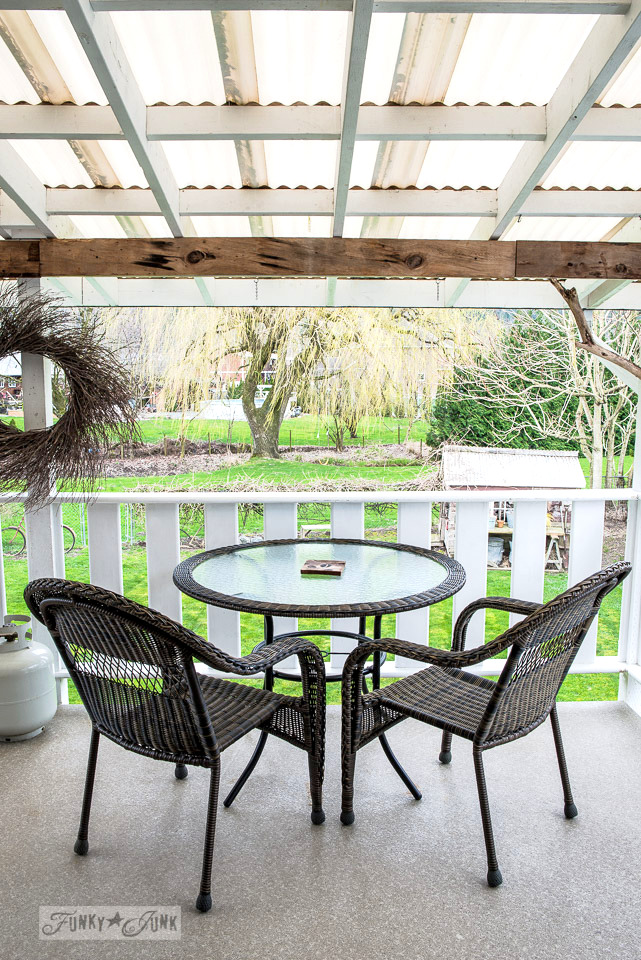 Resin wicker outdoor furniture on a back patio, part of how to spring clean the outdoors through pressure washing with tips