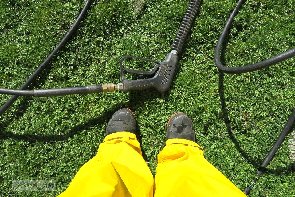 Wearing rain gear and boots to prepare for spring cleaning pressure washing
