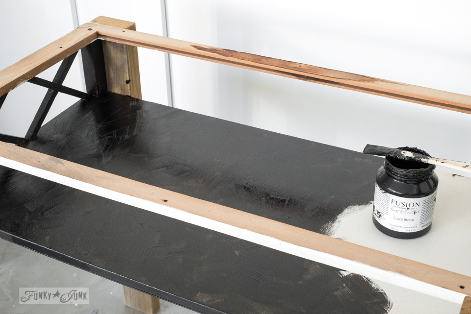 Painting a coffee table and 2x4s with Fusion Mineral Paint's Coal Black while turning a coffee table into a rustic farmhouse flip-up top desk. Click to see the after! #oldsignstencils #funkyjunkinteriors #office #signs #reclaimed