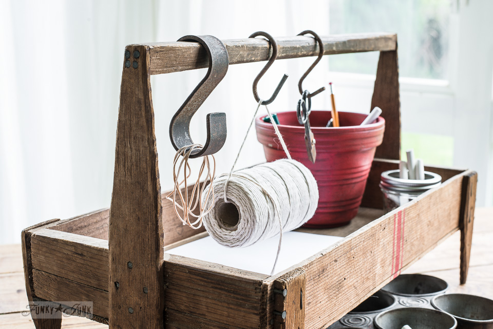 A mini vintage inspired office organizer with S hooks for hanging office gear. Part of Grain sack striped farmhouse tote used 3 ways with Funky Junk's Old Sign Stencils #funkyjunkinteriors #oldsignstencils #grainsackstripes #vintage #toolbox #caddy #tote