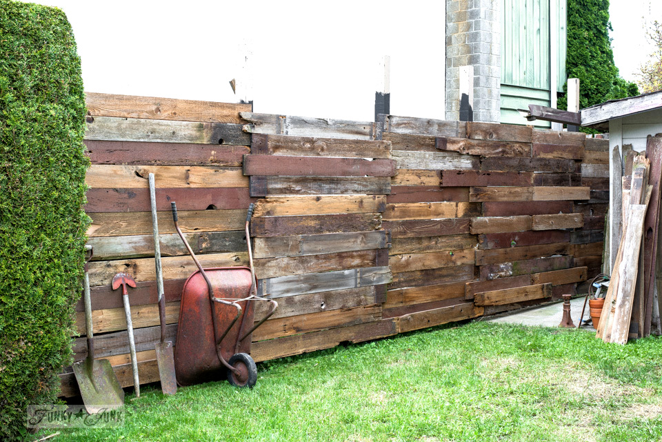 Learn how to build this cool reclaimed wood backyard garden fence! Click to see the finished result!