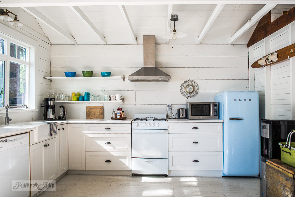 A white kitchen with shelves, Smeg blue fridge, painted floors and planked vaulted ceilings in a dreamy white shiplapped lake cottage at Cultus Lake, BC