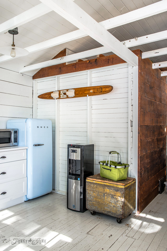 A blue smeg fridge, water ski wall art, painted floors and planked vaulted ceilings in a dreamy white shiplapped lake cottage at Cultus Lake, BC