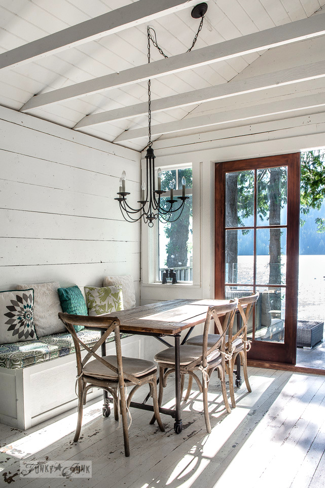 Rustic wood table and chairs, painted floors and a planked vaulted ceilings in a dreamy white shiplapped lake cottage at Cultus Lake, BC