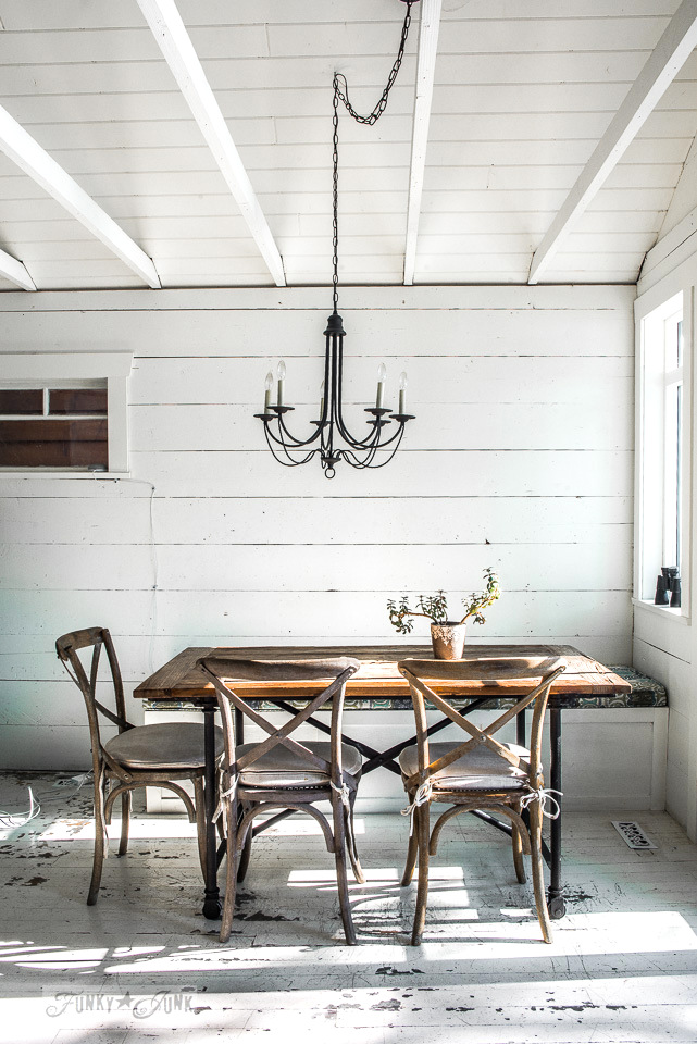 A rustic table and chairs with bench, painted floors and planked vaulted ceilings in A dreamy white shiplapped lake cottage at Cultus Lake, BC
