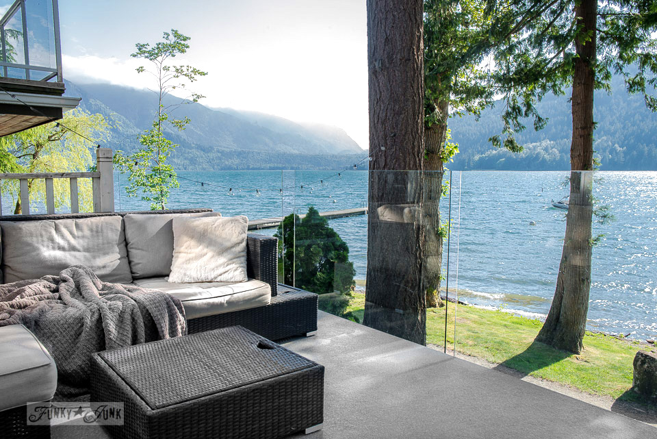 Outdoor sofa overlooking a lake view, at a dreamy white shiplapped lake cottage at Cultus Lake, BC