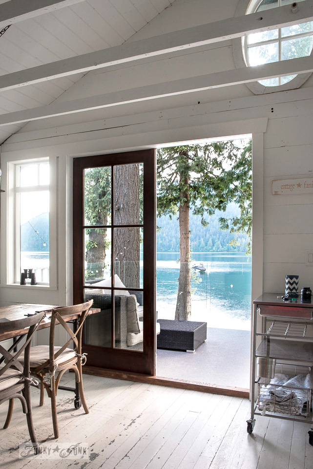 An oval transom window in a peaked planked vaulted ceiling in a dreamy white shiplapped lake cottage at Cultus Lake, BC