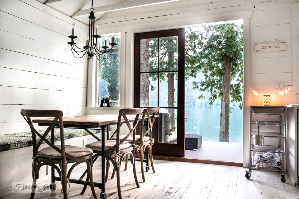Rustic wood table and cross-backed chairs on white painted hardwood floors in a dreamy white shiplapped lake cottage at Cultus Lake, BC