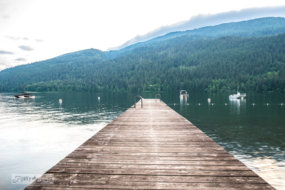 A lake with a mountain backdrop from a wharf at a dreamy white shiplapped lake cottage at Cultus Lake, BC