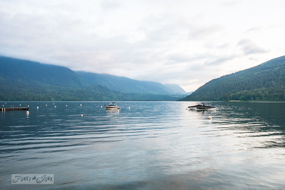 Boats parked in the lake at a dreamy white shiplapped lake cottage at Cultus Lake, BC