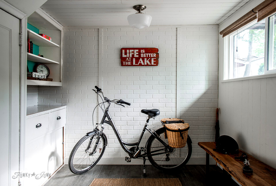 White brick wall in a quaint cottage with a red and white Life is better at the Lake sign - part of A dreamy white shiplapped cottage tour at Cultus Lake, BC