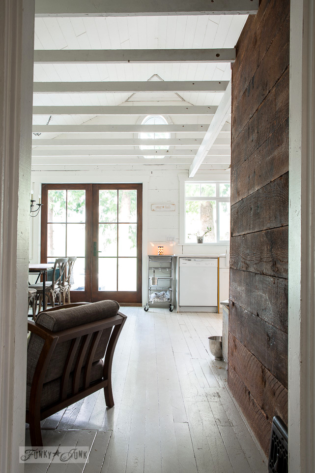 White painted hardwood floors and vaulted ceilings with a reclaimed wood wall in a dreamy white shiplapped lake cottage tour at Cultus Lake, BC