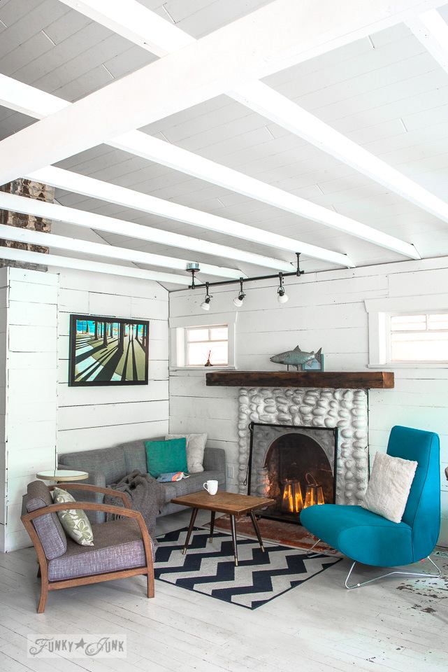 A white painted rock fireplace with wood mantel lit with candles in a living room inside a dreamy white shiplapped lake cottage at Cultus Lake, BC