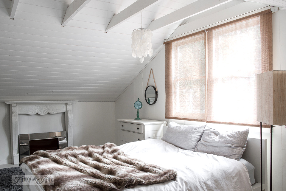 A cozy bedroom with electric fireplace and wood blinds with planked vaulted ceiling in a dreamy white shiplapped lake cottage at Cultus Lake, BC