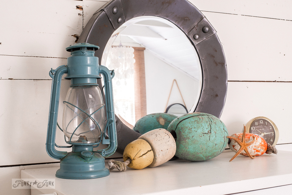 Coastal beach / lake touches of an aqua lantern and pastel buoys in a dreamy white shiplapped lake cottage at Cultus Lake, BC