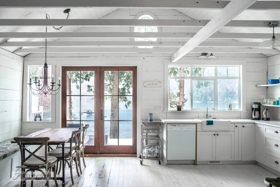 White kitchen with shelving, painted hardwood floors and planked vaulted ceilings in a dreamy white shiplapped lake cottage tour at Cultus Lake, BC