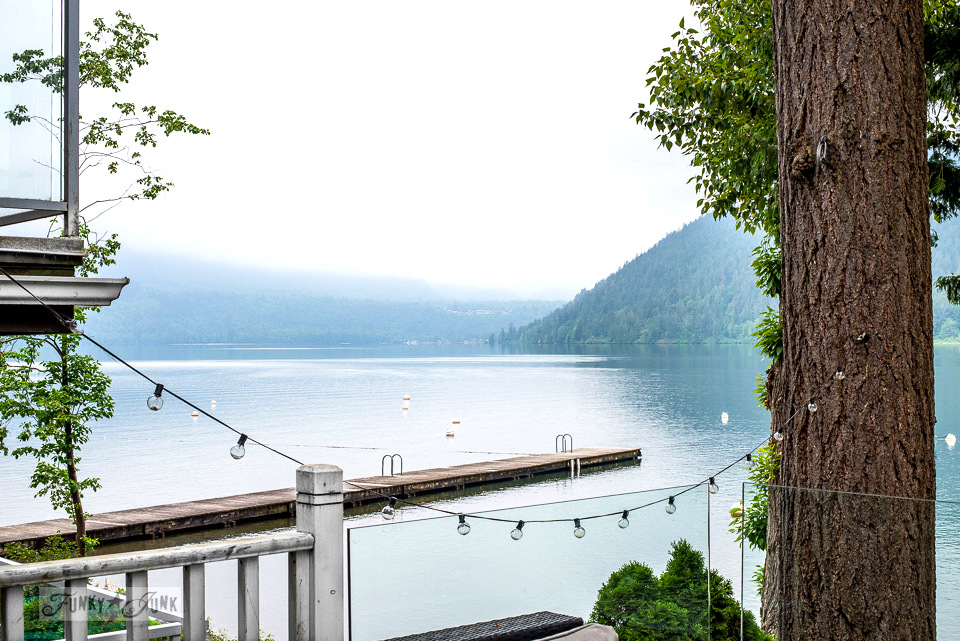 A serene lake view with string lights tied to a tree at a dreamy white shiplapped lake cottage at Cultus Lake, BC