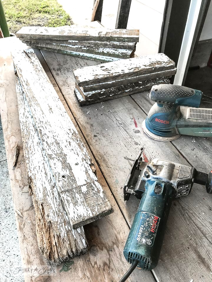 sanding down reclaimed wood chippy white fence planks to create new shelving for a bathroom closet