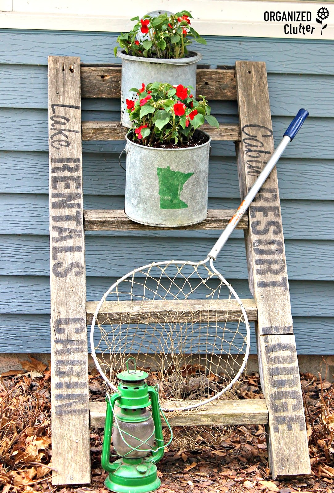 Cabin and lake themed junk garden ladder plant stand by Organized Clutter, featured on Funky Junk Interiors