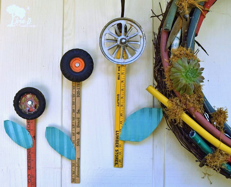 Repurposed wheel and yardstick summer flowers for the garden by Lora B, featured on Funky Junk Interiors