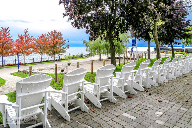 Lined up white adirondack chairs along the waterfront at Ontario Place park during a fall trip to Toronto, Ontario, Canada