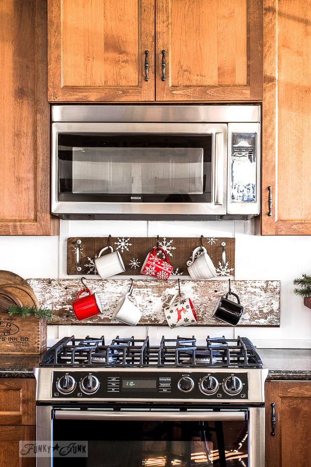 Double decker Christmas cups hanging from s hooks on snowflake and chippy wood planks in a Christmas kitchen home tour.