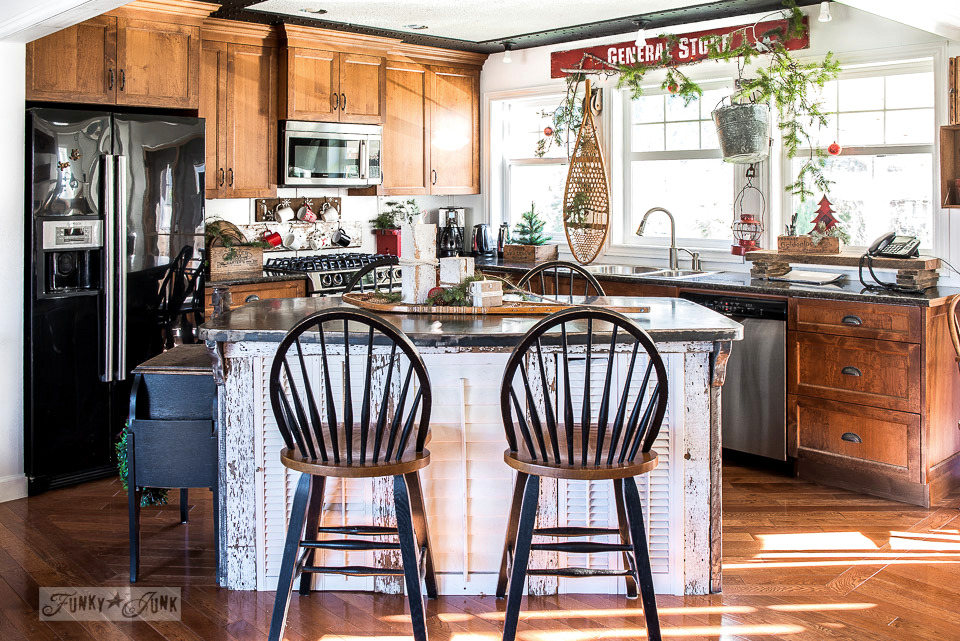 Rustic Christmas kitchen home tour with wood cabinets, white chippy island and red General Store sign - part of a Christmas home tour