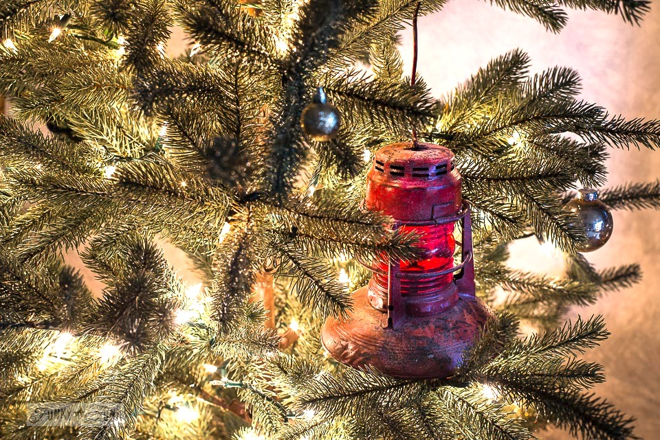 Red vintage train lantern in a Christmas tree - part of a Christmas home tour