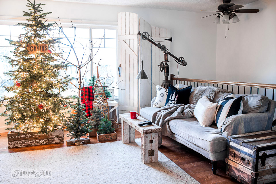 Rustic Christmas tree forest in a livingroom with DIY crate skirt and cozy Ikea Stocksund sofa - part of a Christmas home tour