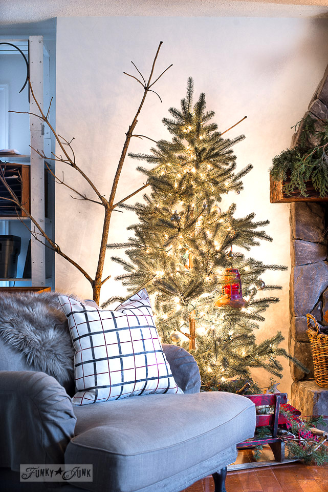 Rustic Christmas tree forest in a livingroom with a plaid black and red pillow - part of a Christmas home tour