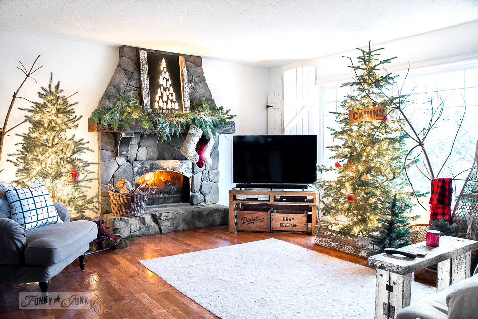 Rustic Christmas tree forest in a livingroom with snowshoes and illuminated Christmas trees mantel sign on a rock fireplace - part of a Christmas home tour.
