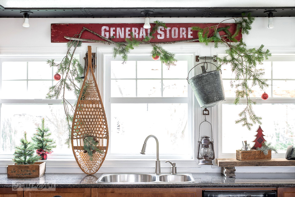 Snowshoes in a forest Christmas kitchen windows with red General Store sign with Funky Junk's Old Sign Stencils and Fusion Mineral Paint