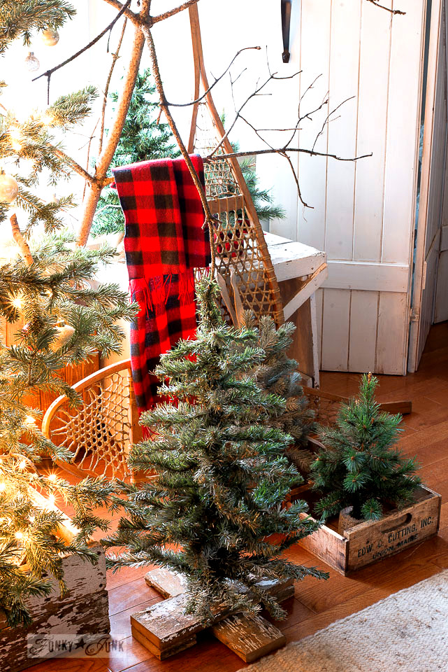 Make this Christmas tree forest with DIY reclaimed wood crate skirt with snowshoes, mini Christmas trees in crates and twiggy branches to get the outdoor look!