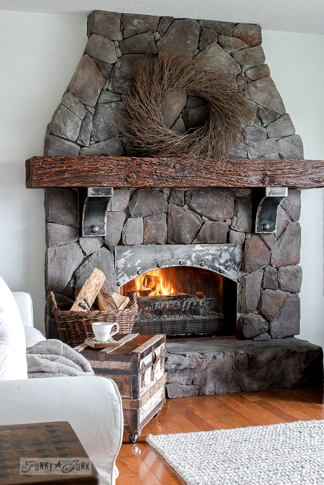 Rock floor to ceiling fireplace with metal accents with an oversized twig wreath in a rustic winter living room