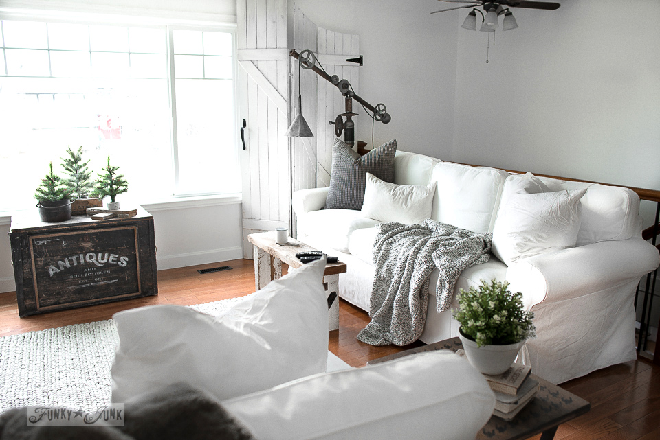 White Ektorp 3.5 Ikea sofas in a winter living room with rustic wood oar wall decor and a rusty junk lamp