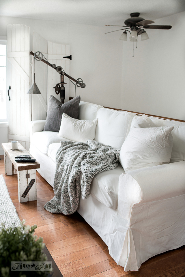 White Ektorp 3.5 Ikea sofas in a winter living room with rustic wood bench and rusty junk lamp