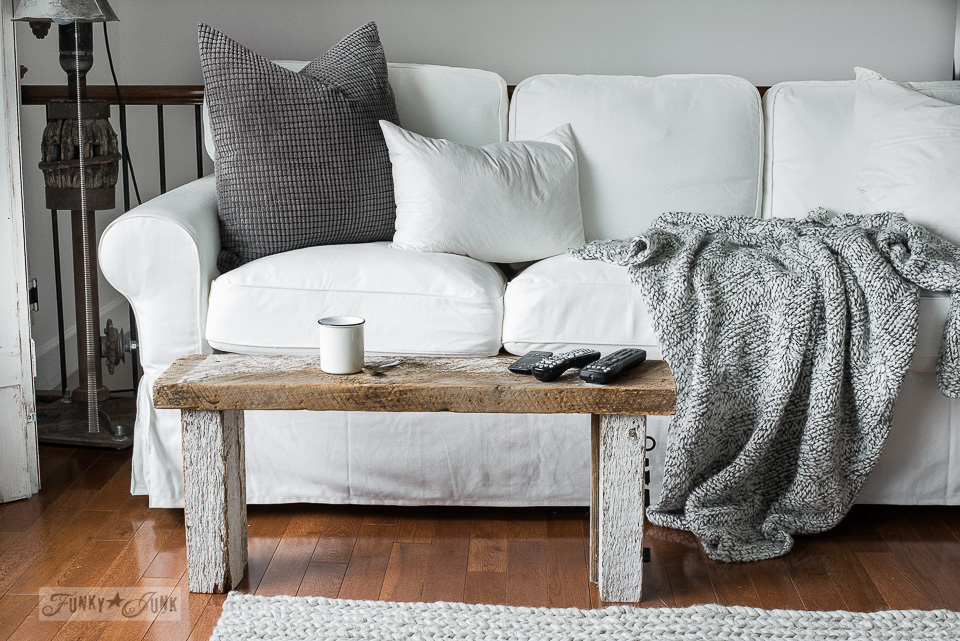 White Ektorp 3.5 Ikea sofas in a winter living room with rustic wood bench