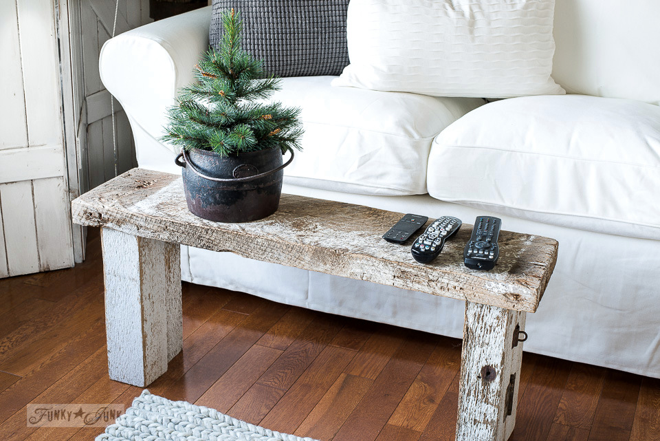A rustic reclaimed wood bench as a coffee table in an Ikea Ektorp white sofa livingroom tour.
