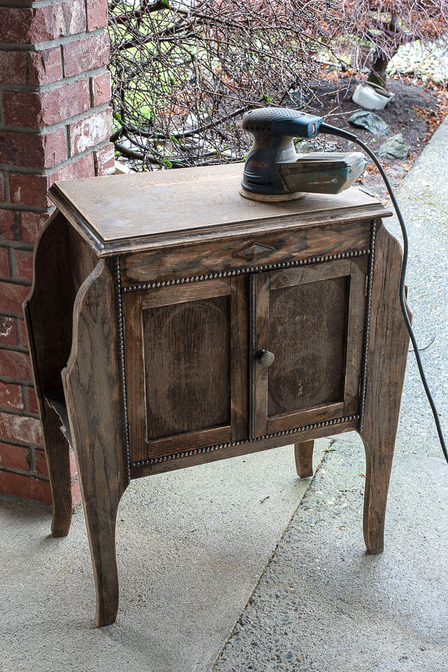A vintage wooden side table found on the curb gets a light sanding to prep it for repainting.