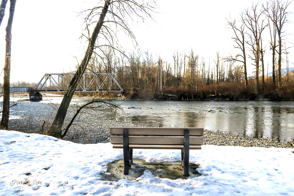 Winter bench looking out towards the trail bridge during a bike ride on the Vedder River Rotary Trail in Chilliwack, BC Canada