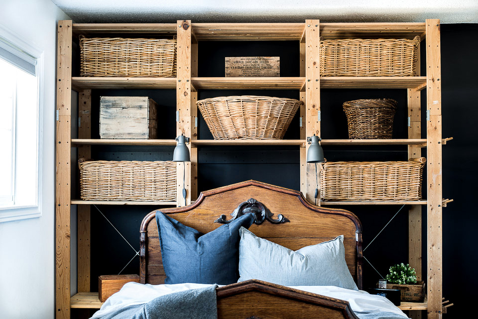 Learn how to frame a black wall with rustic Ikea shelving and basket storage in a bedroom.