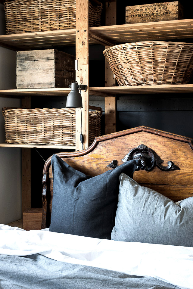 Take the tour of this guest room, with a decadent antique bed and wicker filled shelving in front of a dramatic black wall.