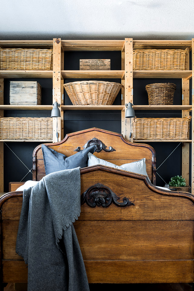 Visit this beautiful bedroom transformation with the addition of an antique wood carved bed against a black wall lined with Ikea Gorm wood shelving and rustic wicker baskets for a dramatic and beautiful effect! #antiques #bed #bedroom