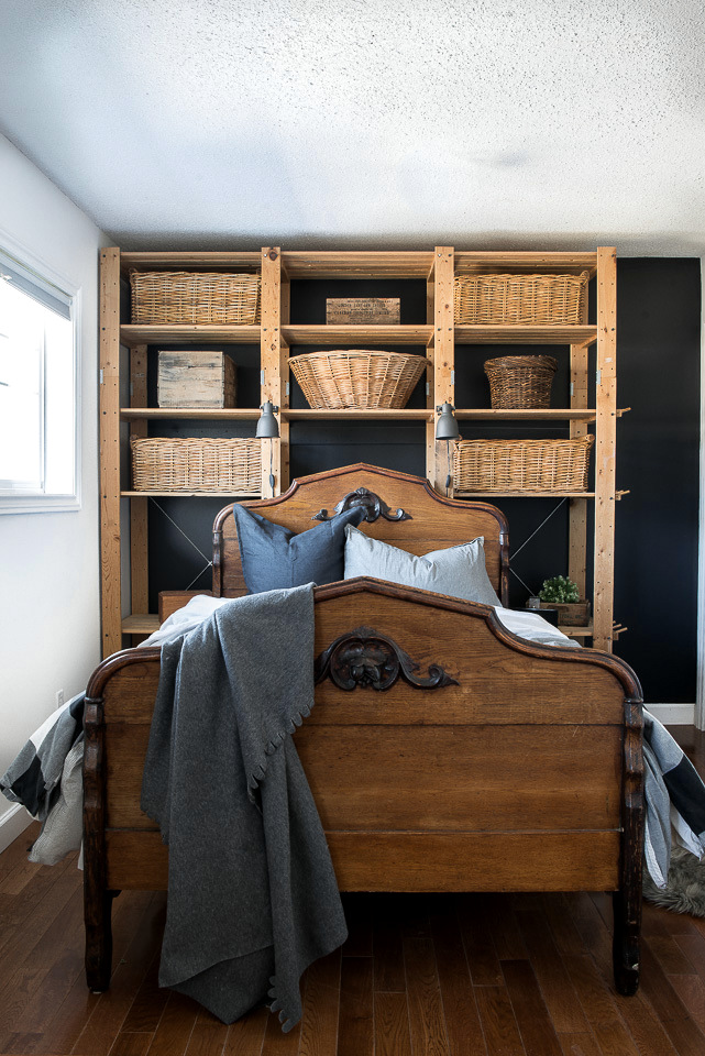 Learn how an antique bed find suddenly transformed a boy's room into a beautiful guest room. Includes black painted wall with Ikea shelving and wicker basket storage. Part of Funky Junk's favorite posts and junk projects of 2019.