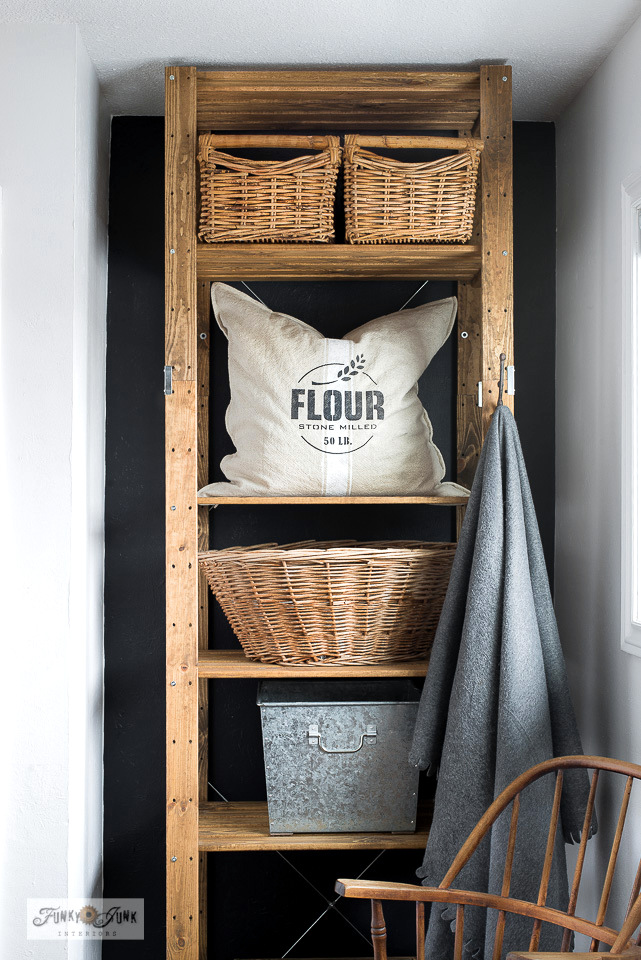 How to turn a new Ikea storage shelf into a rustic farmhouse beauty! The Henjne shelf was stained then stacked with vintage baskets and rustic crates to house laundry, recycling and more! Featuring a stenciled Flour grain sack pillow with Funky Junk's Old Sign Stencils
