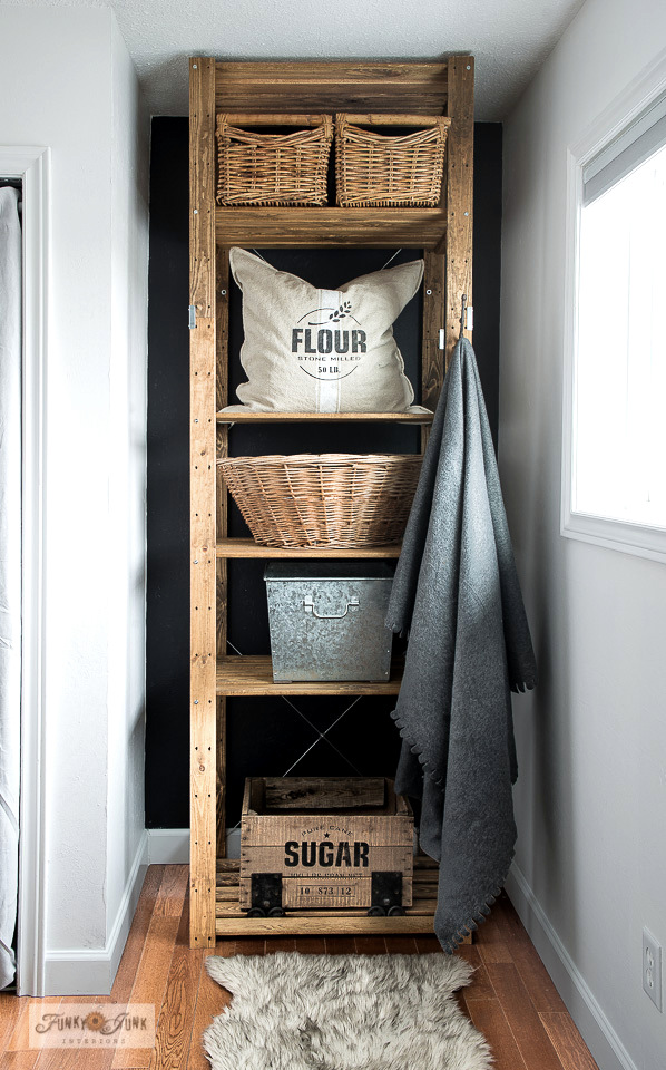 How to turn a new Ikea storage shelf into a rustic farmhouse beauty! The Henjne shelf was stained then stacked with vintage baskets and a crate stenciled with Pure Cane Sugar to house laundry, recycling and more! Showcasing a replicated Flour grain sack with Funky Junk's Old Sign Stencils.