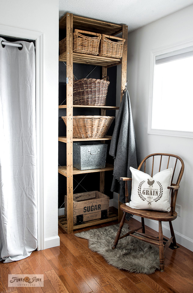 How to turn a new Ikea storage shelf into a rustic farmhouse beauty! The Henjne shelf was stained then stacked with vintage baskets and rustic crates to house laundry, recycling and more! Featuring Sugar and Grain pillow and crate with Funky Junk's Old Sign Stencils